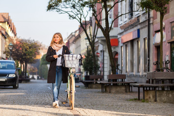 Girl with retro bicycle walking on old town