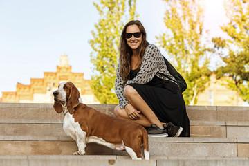 Passeio no parque com o cão Basset Hound em primeiro plano numa linda tarde sentada na escadaria observando o por-do-sol de óculos escuros