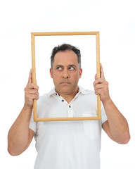 Funny man uses a frame to frame himself. He is overweight and is wearing a white polo..