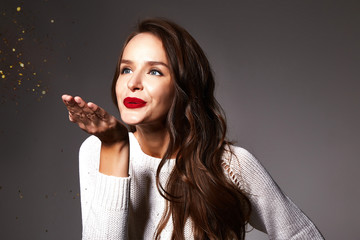 Beautiful sexy young brunette woman with wavy hair bright evening make-up red lips long fluffy eyelashes holds palm with gold sequins in front of her blows them a holiday New Year Christmas joy fun. Wall mural
