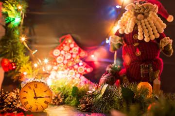 Новогодние декорации. Деревянные часы на фоне новогодних гирлянд и Санта Клауса. Начало двенадцатого. Канун нового года