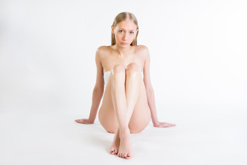 Beautiful slim girl is sitting on a white background