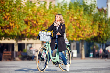 Autumn in the city, woman with retro bike