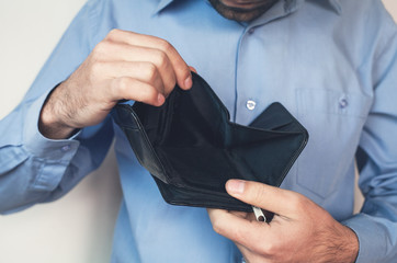 Businessman holding empty wallet.