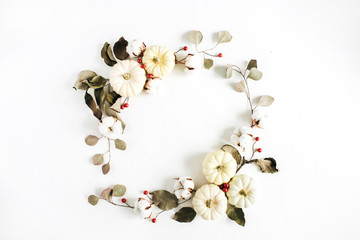 Wreath frame made of white pumpkins, red berries and eucalyptus branches on white background. Flat lay, top view autumn fall composition.
