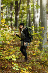 Cheerful brunette tourist girl wears black cap and backpacked have walk through forest holding stick, autumn tourism concept