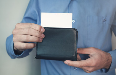 Businessman holding wallet with business card.
