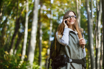 Cheerful brunette tourist backpacked girl have walk through forest holding smartphone, autumn tourism concept