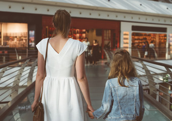 Mom and daughter walking in shopping mall.