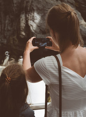 Woman and her daughter doing photos of penguins in the zoo.