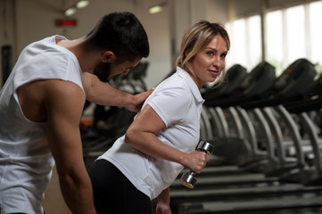 Personal coach with middle aged female in gym