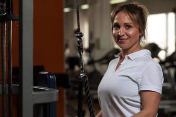 Happy smiling middle aged woman working out in gym