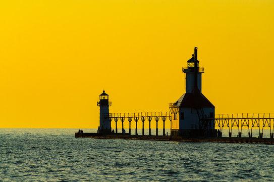 The lighthouse, pier and catwalk at St. Joseph, Michigan silhouetted against a hazy yellow sky