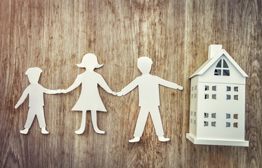 Family and home concept. Paper father, mother and son holding hands near miniature house on wooden background.