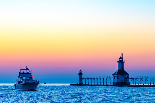A boat motors into the river past the St. Joseph, Michigan, lighthouse and pier at sunset