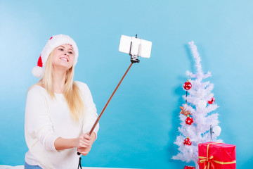 Girl in santa hat taking picture of herself using selfie stick