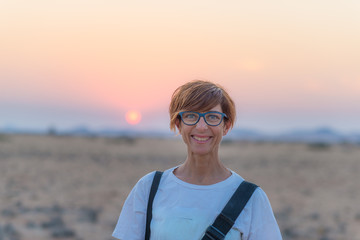 Portrait of a red haired woman with green eyes, eyeglasses and smiling facial expression. Sunset at the horizon. Shot outdoors with natural background.