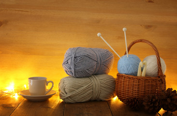 warm and cozy yarn balls of wool and hot cup of coffee on wooden table.