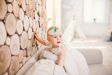 little blue-eyed girl blond in a white tulle dress with a decoration on her head playing and rejoicing on a beige sofa in a room with decorative wooden wall in the form of hemp