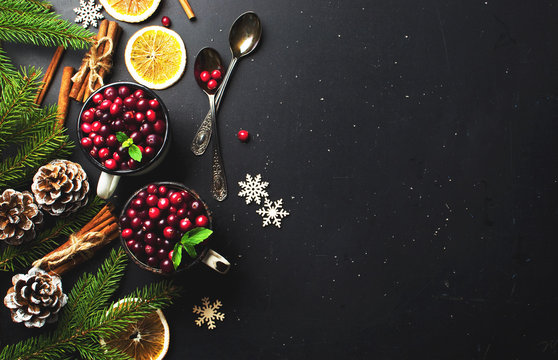 Fresh red cranberries in a white cup, cinnamon sticks, dried orange circles, spruce branches and snowflakes on a black background with copy space top view. Christmas holidays background.