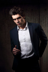 Sexy handsome male model posing in blue fashion suit and white style shirt on dark shadow background