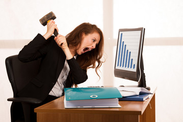 Angry business woman expressing rage at her desk in the office