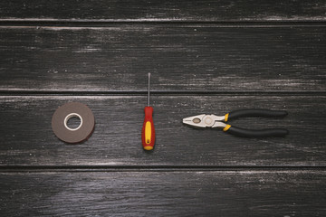 Top view of Working tools - screwdriver, pliers and duct tape on the wooden background