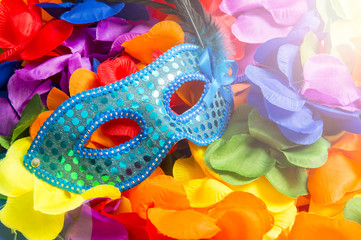Sequined blue carnival mask sits on bright background of rainbow colored flower leis