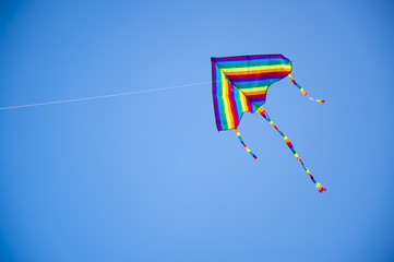 Colorful rainbow striped kite flying in a clear blue sky