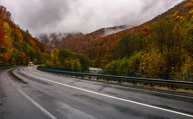 curve road through mountains on autumn rainy day. overcast sky over the forest in red foliage. yellow bus, with turned lights, ride on wet asphalt