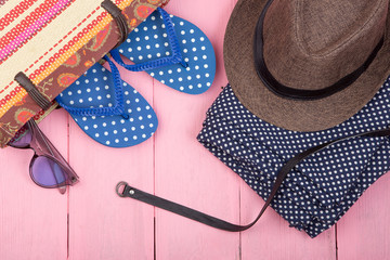 Summer accessories - sunglasses, straw beach bag, pants, sun hat, belt and flip flops on pink wooden table