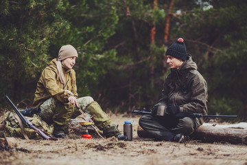 Two hunters are eating together in the forest. Bushcraft, hunting and people concept