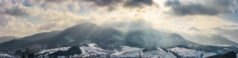 mountain ridge in light beams on cloudy winter day. gorgeous countryside panorama