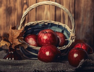 Autumn composition with fresh red apples in a wooden basket on rustic wooden background. Red apples on linen background