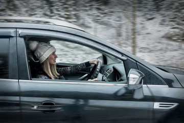 Woman at winter time. Yoyng female sitting and driving in black