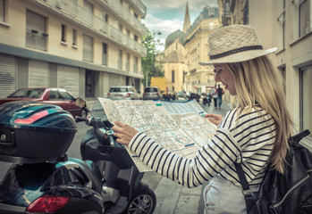 Woman tourist on the street in Paris, look on map under sunlight