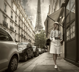 Woman tourist with camera on the street near the Eiffel tower in