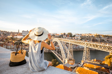 Young woman tourist enjoying beautiful landscape view on the old town with river and famous iron bridge during the sunset in Porto city, Portugal Fototapete