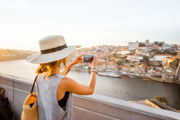 Young woman tourist photographing with phone beautiful landscape view on the old town with river and famous iron bridge in Porto city, Portugal