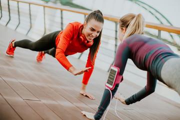 Women doing plank on riverside after running
