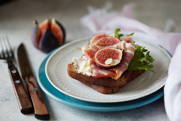 Sandwich with ham, ricotta cheese and figs on white plate
