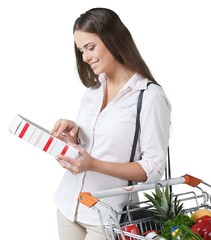 Portrait of a Woman Checking Food Labelling with Shopping Cart