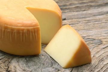 Cheese wheel on wood Organic food