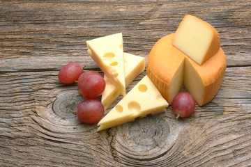 Cheese and grapes. Isolated on wooden table