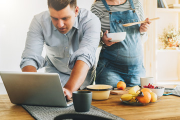 Young married couple in kitchen. Man stands near table and uses laptop, pregnant wife is standing next to him, holding bowl and spoon in his hands and looking at computer screen. Lifestyle.