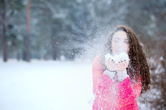 Beautiful woman blowing on the snow