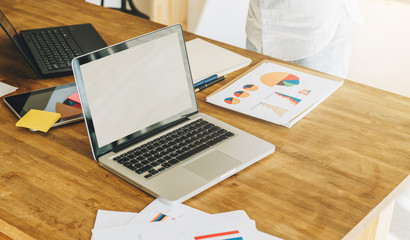 Office, desk. Close-up of a laptop on a wooden table. Nearby are paper graphics, charts, diagrams, a digital tablet, cup of coffee. Space for text, logo. Online marketing, education, e-learning.