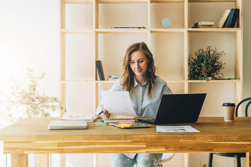 Young businesswoman woman is sitting at kitchen table, reading documents,uses laptop,working, studying.On table tablet computer, paper graphs. Student studying.Online marketing, education, e-learning.