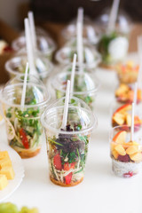 Mini desserts and microgreen salad canapes vegetable snacks in plastic cups canaps. Catering arranged table
