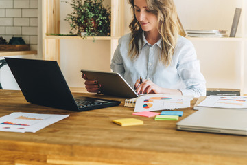 Young businesswoman woman is sitting at kitchen table and uses tablet computer, working, studying. On table laptop, paper documents. Freelancer works at home. Online marketing, education, e-learning.